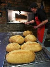 A baker removing the fresh bread from the 1860 wood fired oven at the Ross Village Bakery