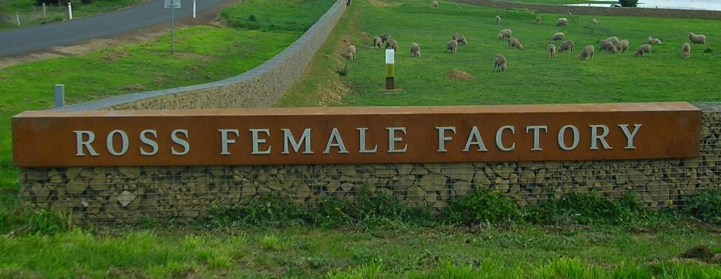 Female Factory sign on rock wall fence