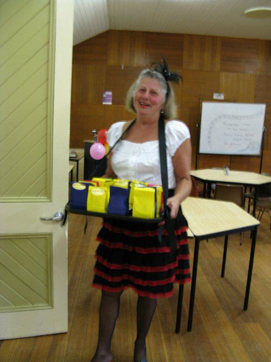 candy seller at the opening of the Midlands Film Society. A lady in costume carrying a tray of lolly bags.